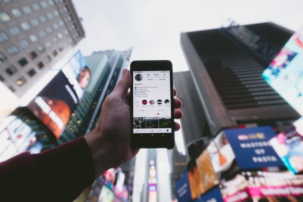 un homme montre son profil instagram à New York